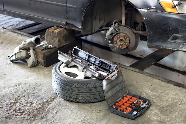 차고에 있는 자동차 브레이크 부품, 바퀴가 닫히지 않은 자동차 브레이크 디스크. 집 차고에 있는 오래된 차의 교체용 바퀴.