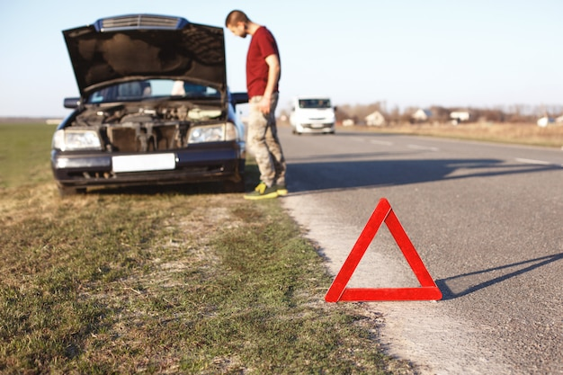 Car breakdown concept. helpless man driver stands near broken auto with opened hood, has problems with engine