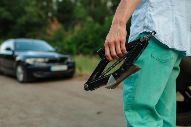 Поломка автомобиля, мужчина держит в руках домкрат.
