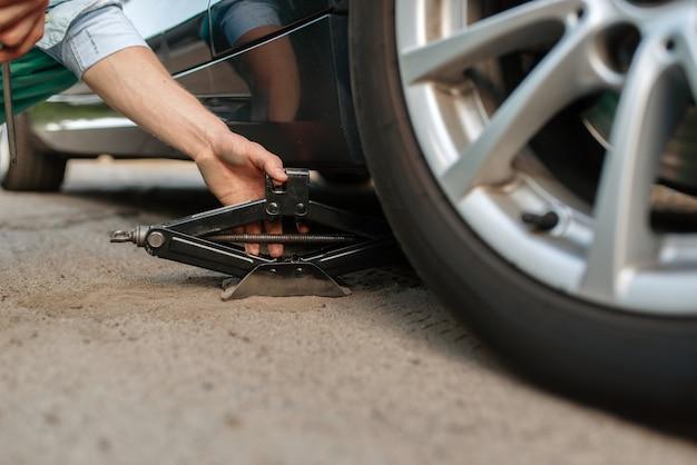 Поломка автомобиля, мужчина ремонтирует спущенное колесо.