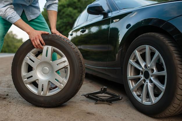Car breakdown, man puts the spare tire.