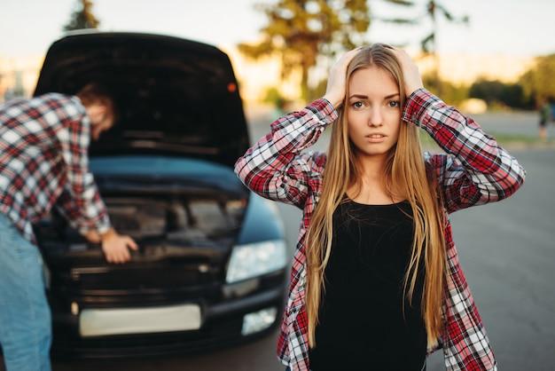 Поломка автомобиля, грустная женщина-водитель против открытого капота