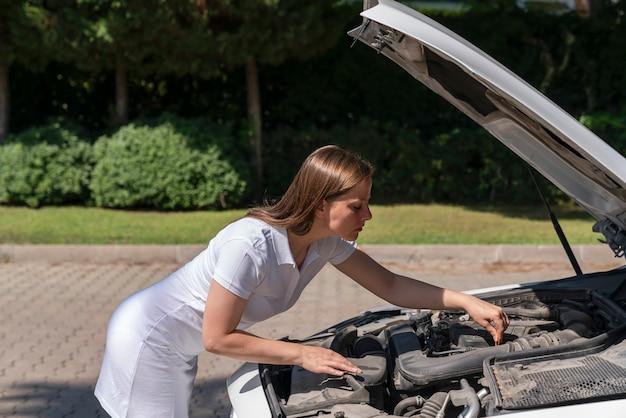 Поломка машины. женщина подняла капот машины, наклонилась над двигателем и пытается самостоятельно диагностировать причину поломки и отремонтировать машину.