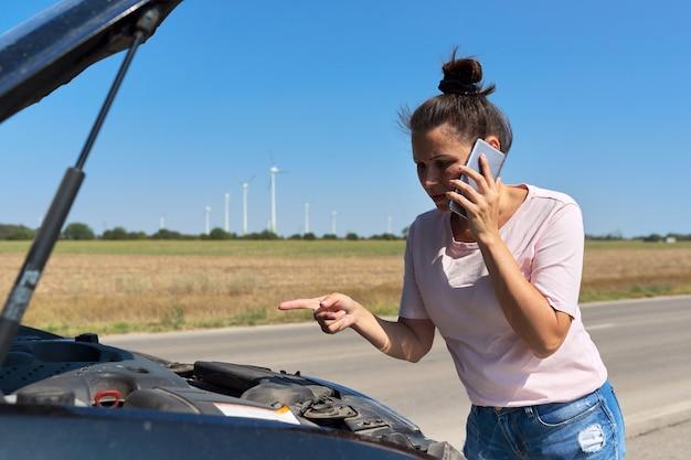 車の故障、携帯電話で話している開いた車のボンネットと道路上の不幸な女性。車の修理サービス、輸送、レッカー車の呼び出し