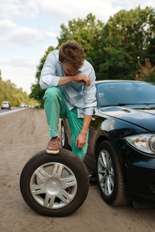 Car breakdown, young man puts the spare tyre. broken automobile or problem with vehicle, trouble with punctured auto tire on highway