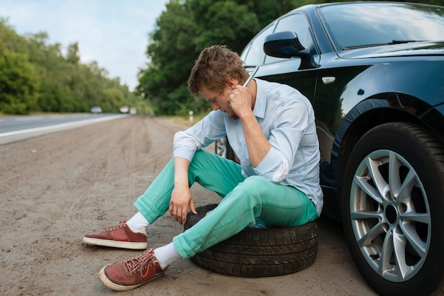 Car breakdown, young man sitting on spare tyre. broken automobile or problem with vehicle, trouble with punctured auto tire on highway