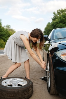 Car breakdown, young woman puts the spare tyre.