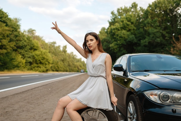 Поломка машины, голосование молодой женщины на дороге.