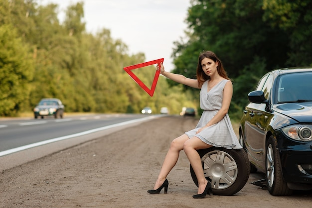 Car breakdown, young woman with emergency stop sign vote on the road