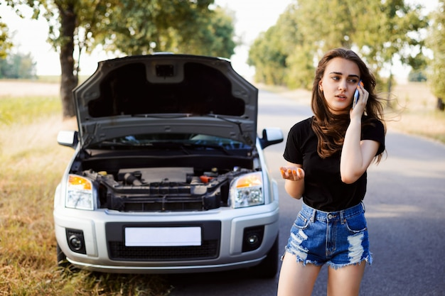 車がアスファルト道路の道端で故障し、若い学生ドライバーが救助チームを呼び出して彼女を助け、車を修理します