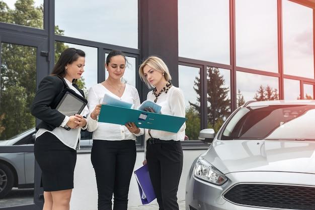 Процедура покупки автомобиля. женщина-дилер с планшетом и покупатели с папкой, стоящей возле автомобиля Premium Фотографии