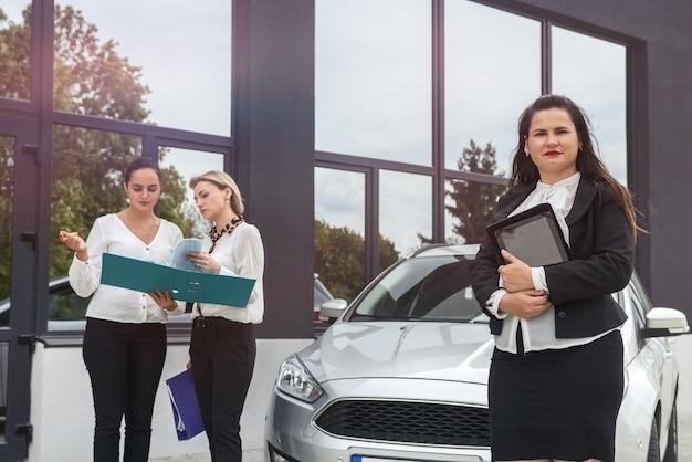 Процедура покупки автомобиля. женщина-дилер с планшетом и покупатели с папкой, стоящей возле автомобиля