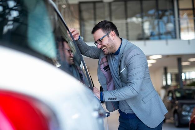 Покупатель автомобиля выбирает свой любимый автомобиль в автосалоне