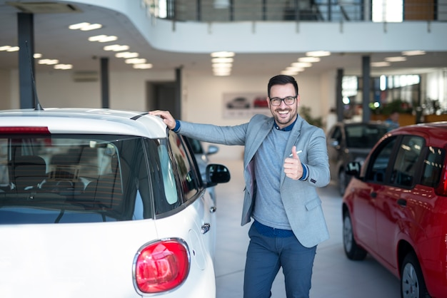 Car buyer with thumbs up standing by the new vehicle in car dealership showroom.