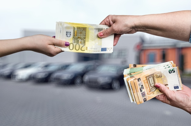 Car buying concept, female hands with euro notes