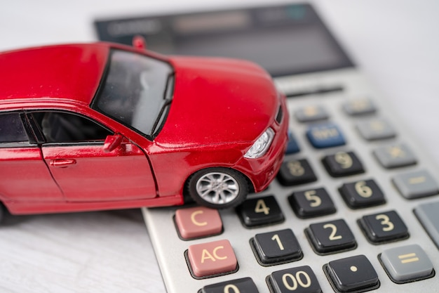 Car on calculator, car loan, finance, saving money, insurance and leasing time concepts.