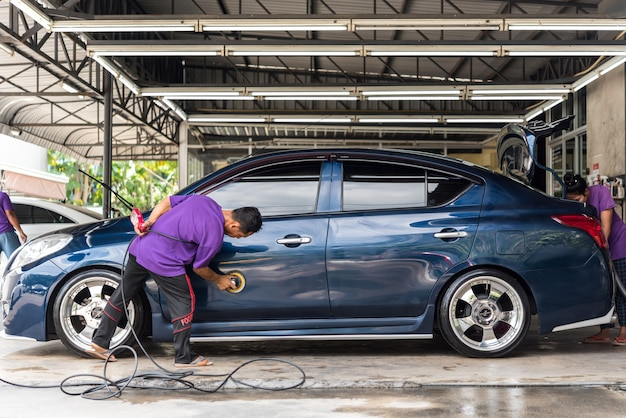 Car care staff cleaning the car (car detailing).