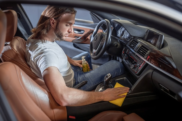 자동차 관리. 젊은 수염 심각한 열정적 인 남자는 운전석에 차에 앉아있는 동안 조심스럽게 표면을 닦아