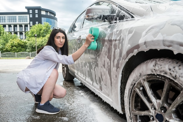Car clean  girl with sponge and foam wash her auto