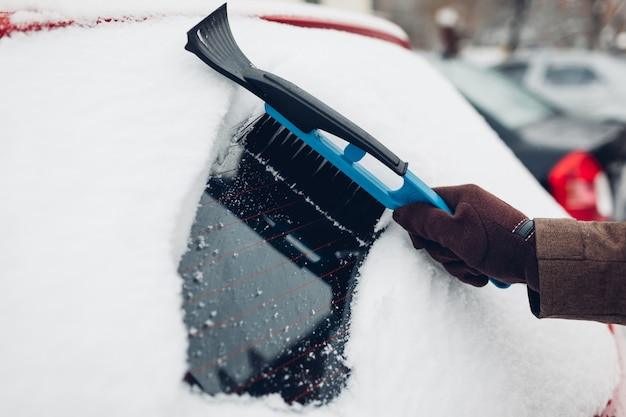 Car cleaning from snow using broom. man taking care of automobile removing ice with brush outdoors