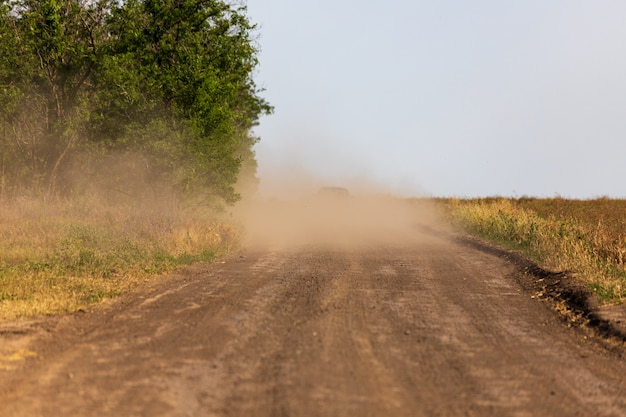 A car in a cloud of dust, driving off into the distance along a rural road between a field and trees