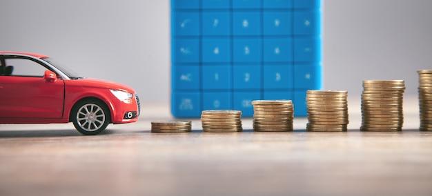 Автомобиль, монеты и калькулятор на столе
