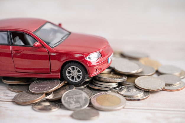 Car on coins background car loan finance saving money insurance and leasing time