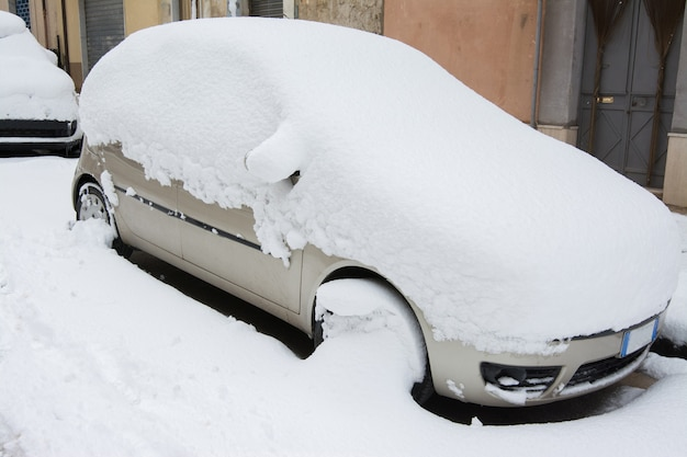 Car covered and surrounded by snow drifts after a snow storm