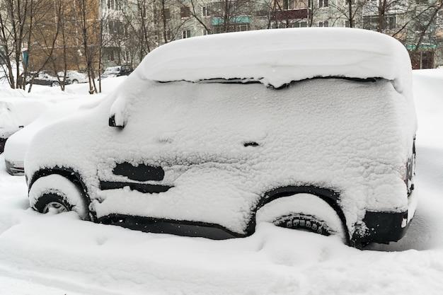 冬の吹雪の後、雪に覆われた車