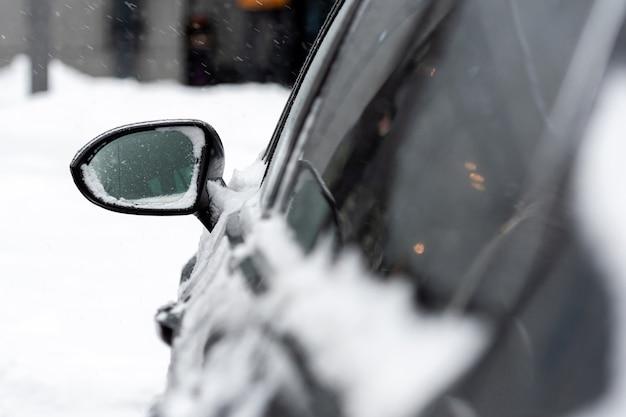 Автомобиль засыпан снегом после шторма, крупный план, выборочный фокус, фокусировка в зеркале заднего вида