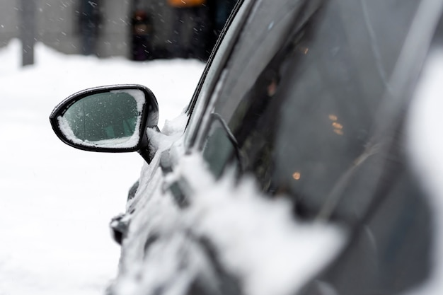 Car covered with snow after storm, close-up, selective focus, focus on the rear view mirror