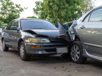 Car crash accident on street with wreck and damaged automobiles.
