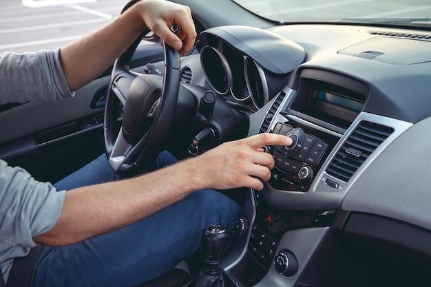 Панель приборов автомобиля. радио крупным планом. человек устанавливает радио