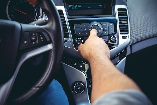 Car dashboard. radio closeup. man sets radio