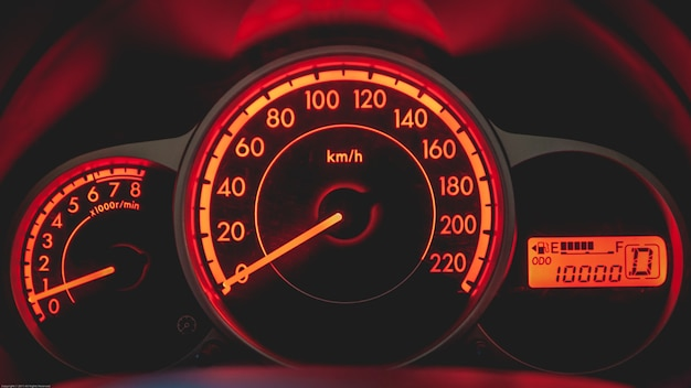 Car dashboard with speedometer and tachometer in orange color