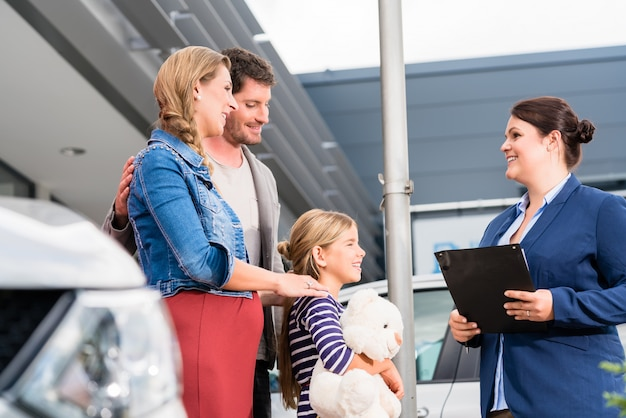 Car dealer advising family on buying auto