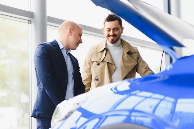 ディーラーで販売されている新車のボンネットの下を見ている車のディーラーと彼のエールのクライアント。若い男が車のサロンで自動車を購入