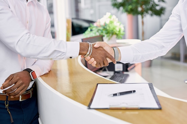 Car dealer and client are shaking hands