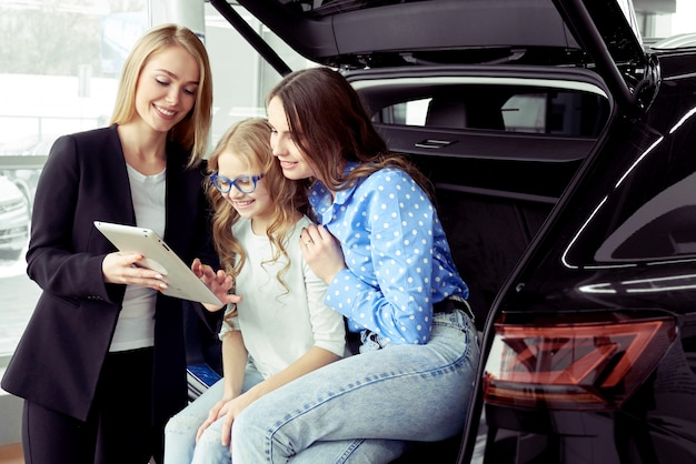 Car dealer consulting woman with daughter in auto salon