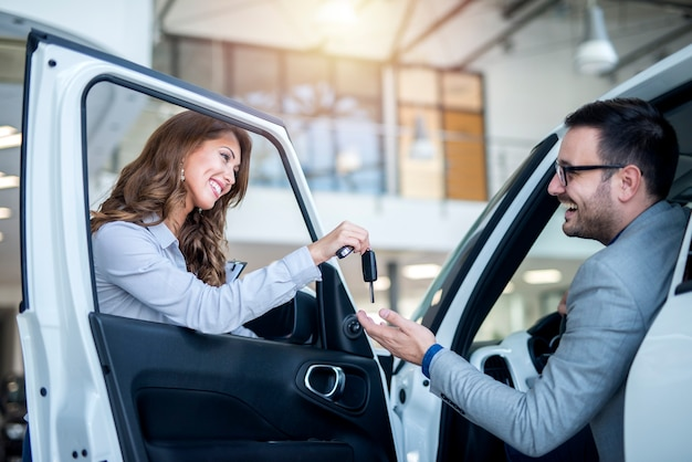 Car dealer and customer at vehicle showroom choosing new car
