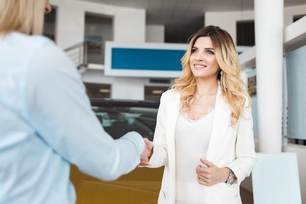 Car dealer in dealership greets beautiful  customer