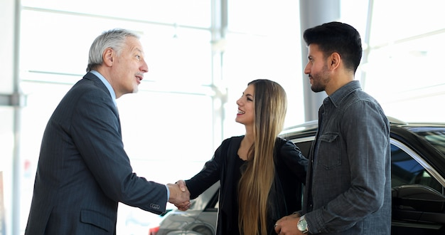 Car dealer giving a handshake to a young couple