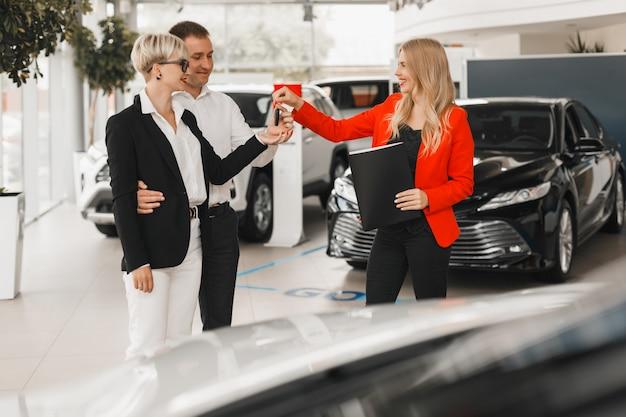 Car dealer giving key for couple  standing in car dealership.