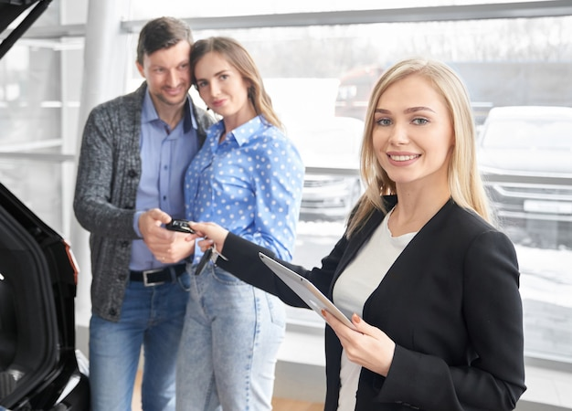 Car dealer giving keys to couple, man and woman buying car.