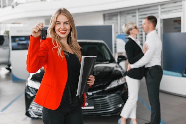 Car dealer holding a key standing against car. couple in a backdrop blurring .
