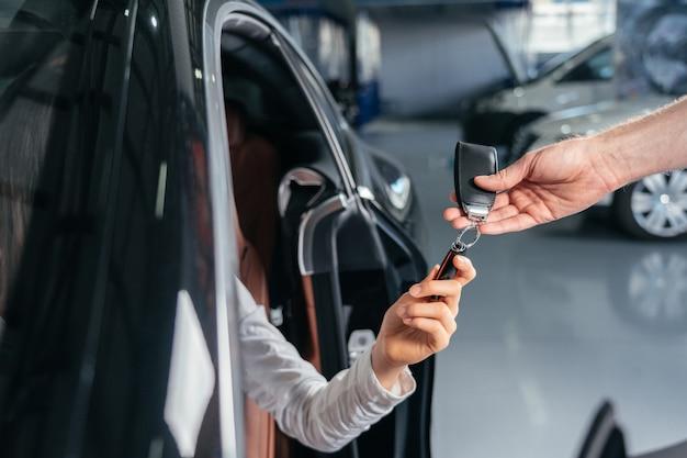 車のディーラーは若い女性に新しい車の鍵を与えています
