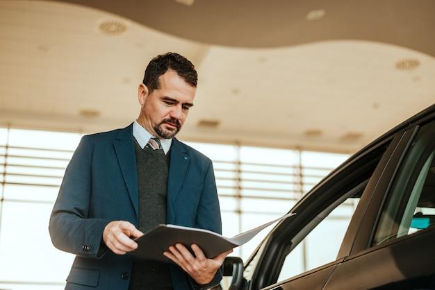 Car dealer looking at notepad in car salon.