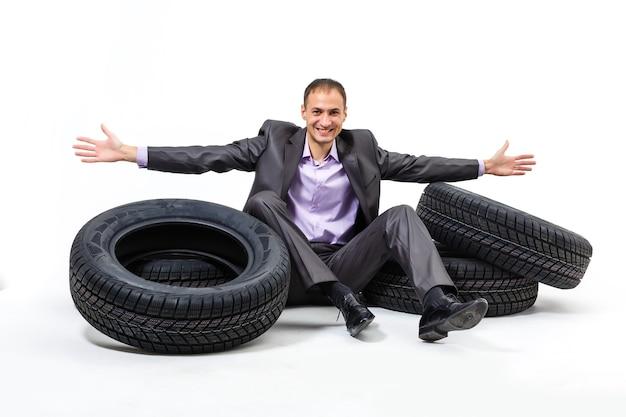 Car dealer man over tire tire background. auto maintenance.
