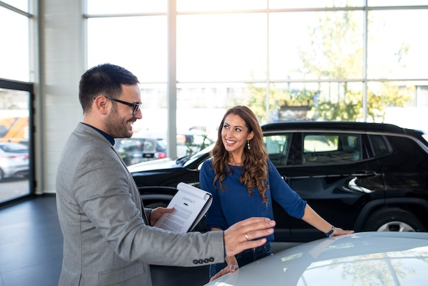 Car dealer presenting new car to the customer