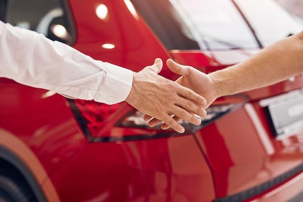 買い手の手を振る自動車ディーラー